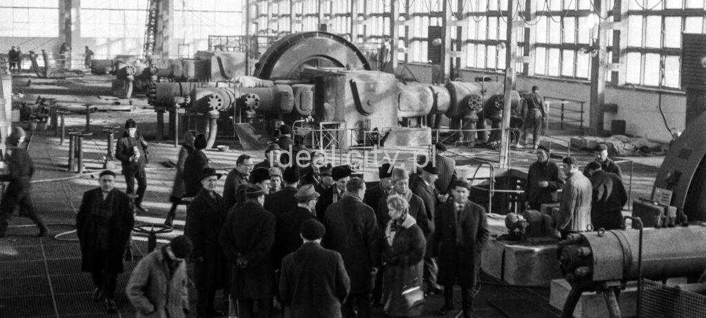 Delagats in coats visit the factory hall.