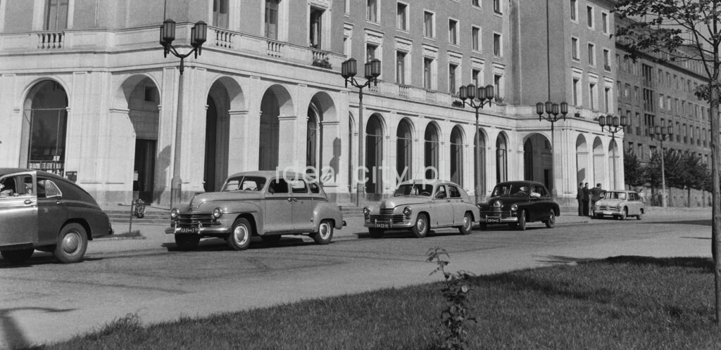 A number of cars are waiting at the taxi stand, monumental architecture in the background.