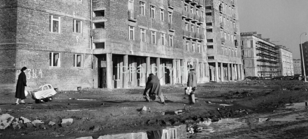 Parents with children in front of an unplastered apartment block.