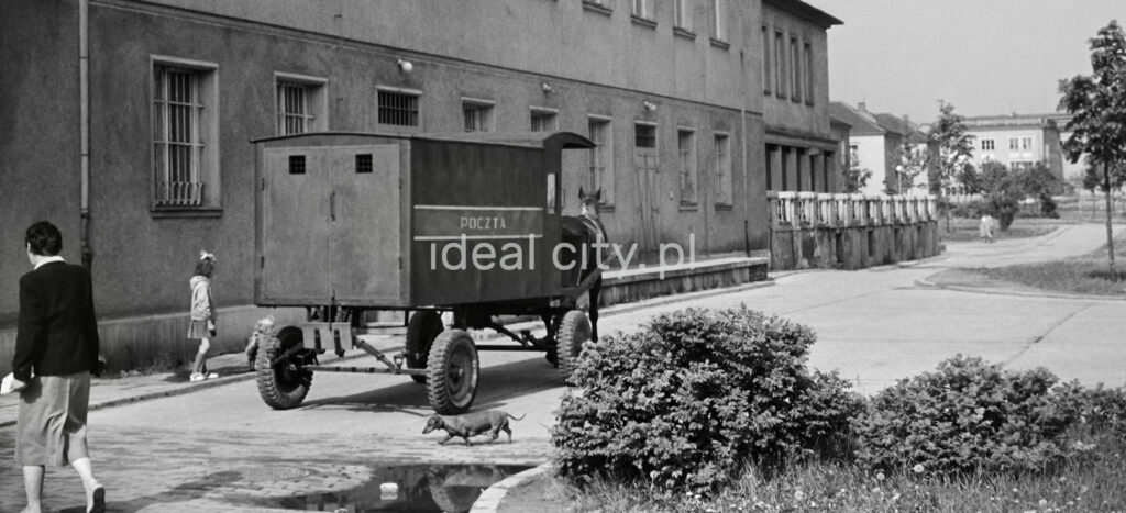 A horse-drawn postal cart goes along the building., passers around.