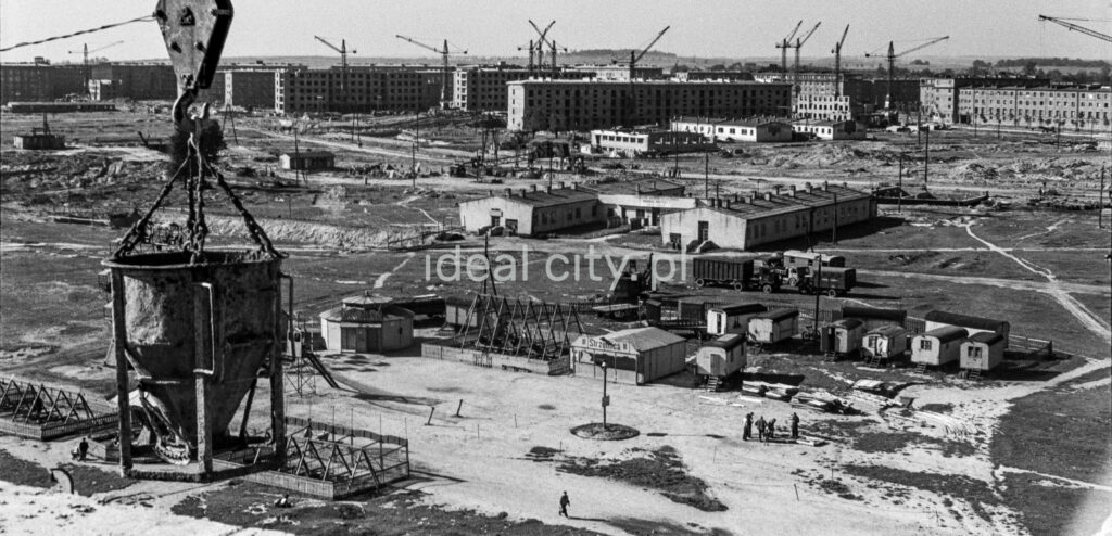 A view of the building barracks from above, in the foreground a pear with concrete hanging from a crane.