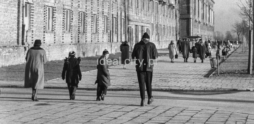 Rear shot of pedestrians walking along a wide sidewalk.