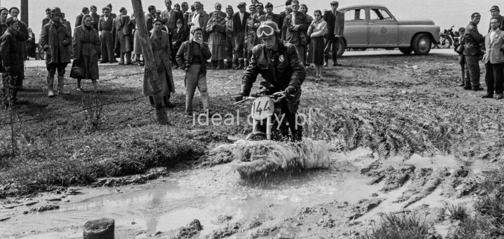 48/5000 The motorcyclist drives into a mud ditch with onlookers in the background.