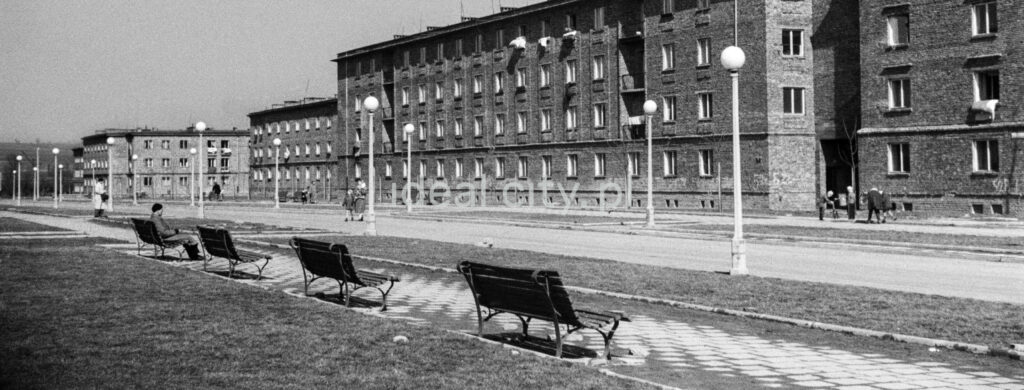 Row of benches along the pedestrian passage by the strett, block of flats in the background.