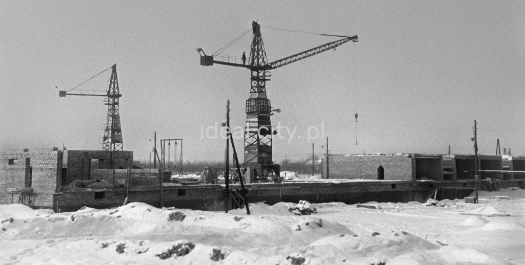 Winter view of two wooden construction cranes.