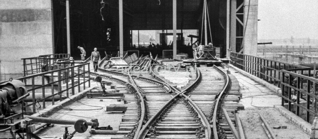 Perspektywa plątaniny torów kolejowych prowadzących do hali fabrycznej.