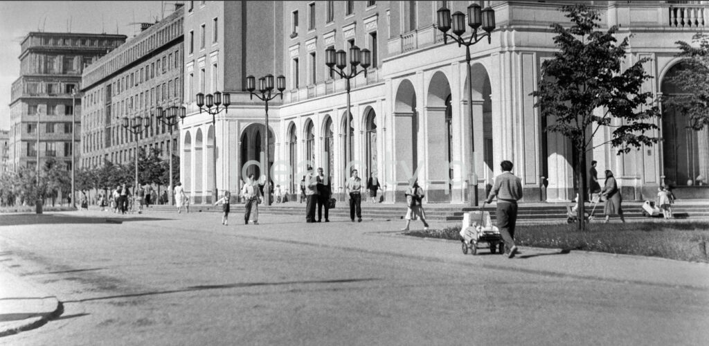 Pedestrian traffic in front of monumental buildings with arcades.