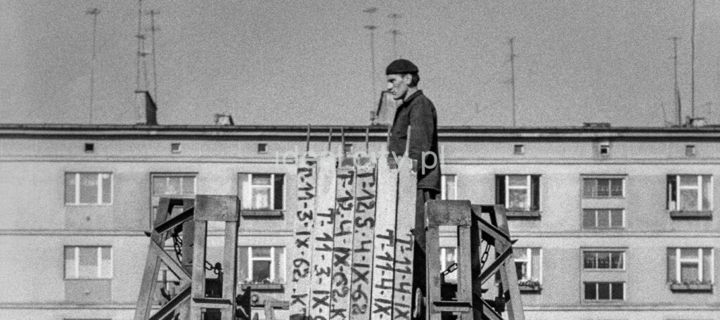 A man in work clothes and a beret protrudes in a monumental manner above the prefabricated panels gathered in front of the apartment block.
