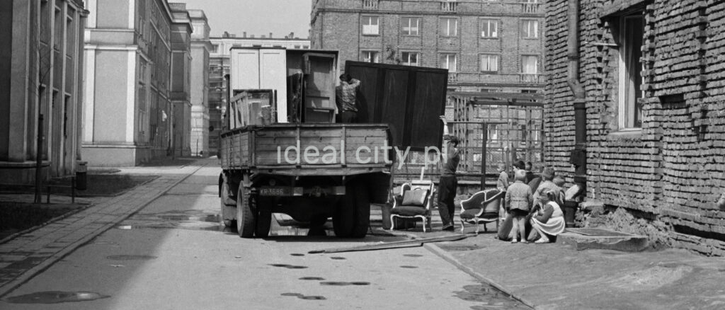 Several men are unpacking furniture from the transport car.