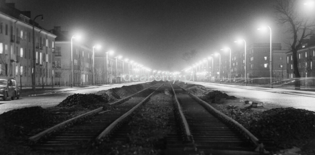 A night perspective of the street, photographed from the center of tram tracks, with apartment blocks on the sides.