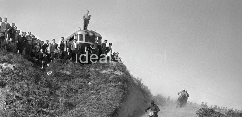 Motorcyclists rush down the gravel road, onlookers rush above.