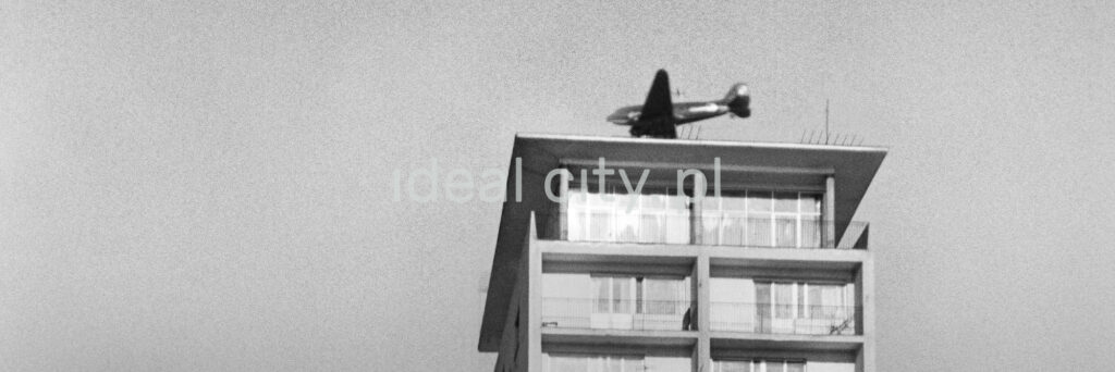 The bottom shot of the plane flying over the roof of the skyscraper.