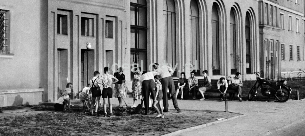 People in everyday clothes perform community work on the lawn in front of the apartment building.