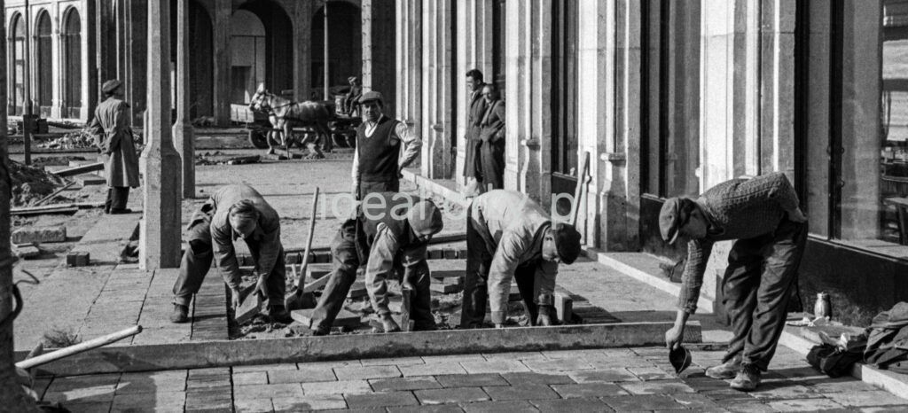 57/5000 Workers in working clothes are laying paving slabs.