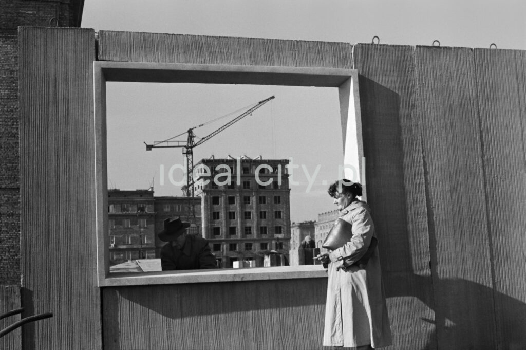 A woman in a trench coat and a briefcase under her arm stands against a prefabricated wall with a window opening.