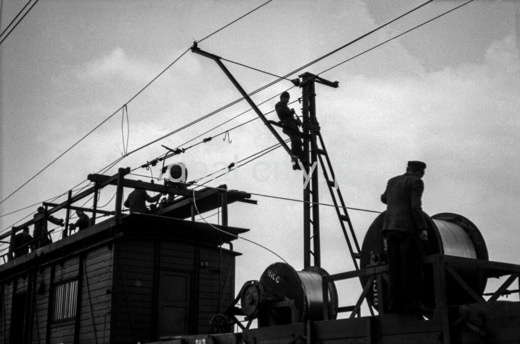 The workers, standing on the wagon's transport platform, assemble the cables.
