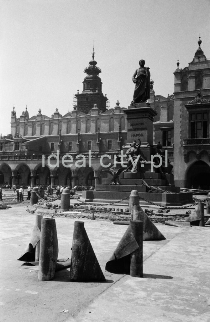 Freely arranged, unfolding rolls with tar paper, on the square of the city square with Renaissance buildings and a monument in the background.
