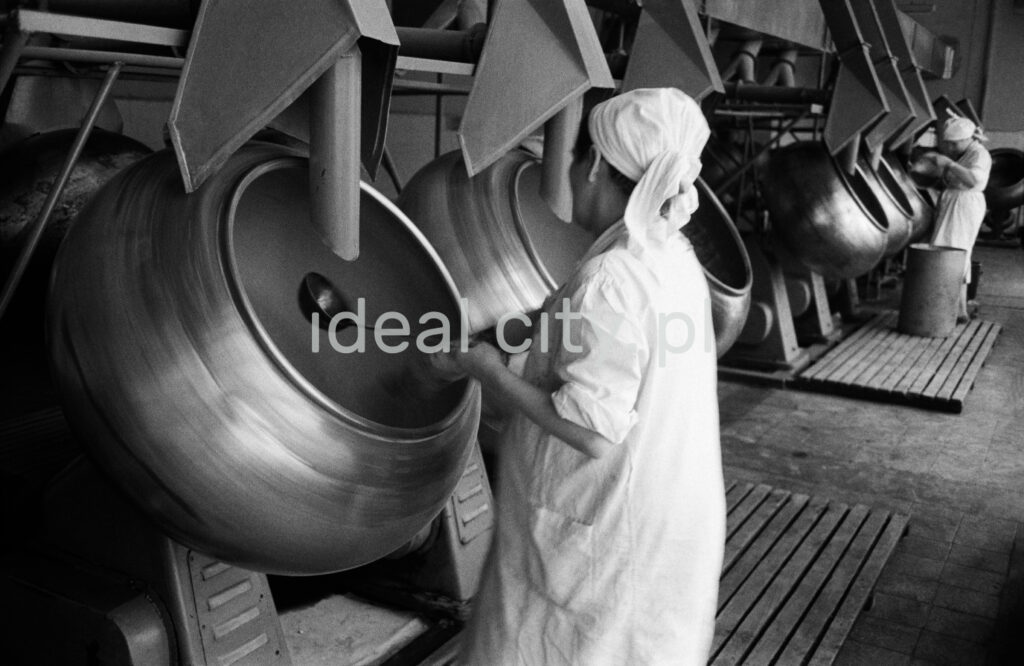 A woman in an apron is mixing with a ladle in rotary boilers.