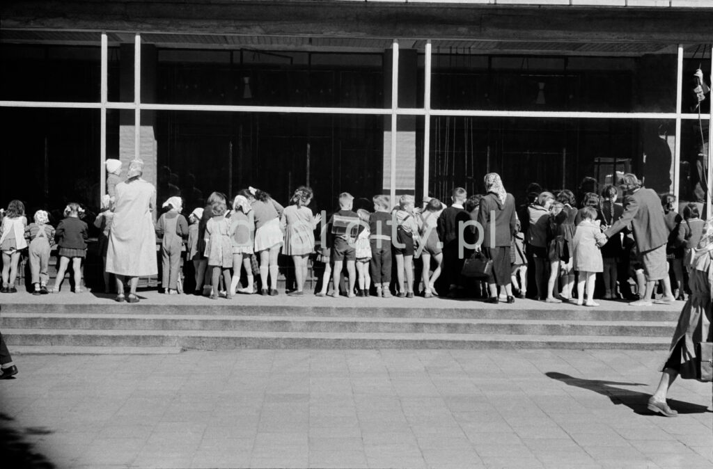 A group of children and several women look through the window into the interior of a shop on the ground floor of a modernist building.