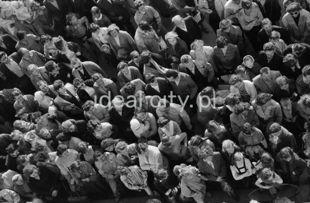 A view from the height of the first floor of the crowd gathered below it, looking into the lens.