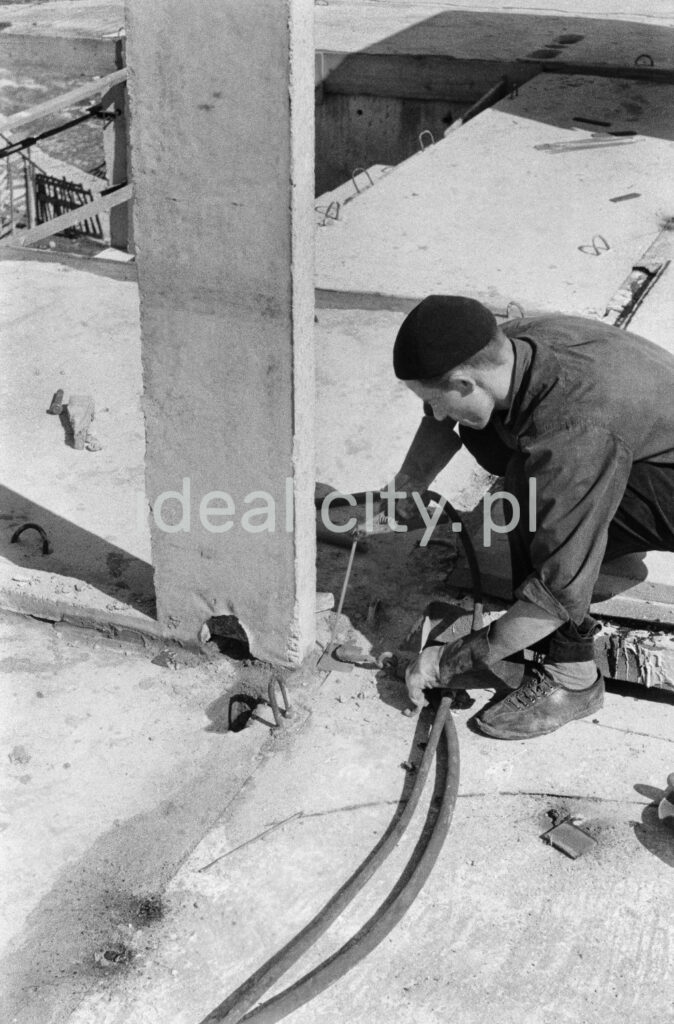 A man in work clothes and a beret on his head and with a cigarette in his mouth welds the elements of the base of the construction pole.