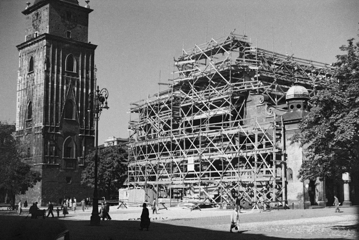 Ujęcie przedstawia fragment Wieży Ratuszowej na Rynku Głównym w Krakowie oraz Sukiennice skryte za warstwą rusztowań.