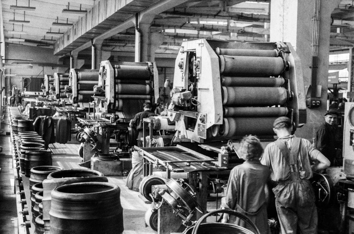 Kobieta i mężczyzna w hali fabrycznej doglądają ustawione szeregowo taśmowe maszyny produkcyjne.