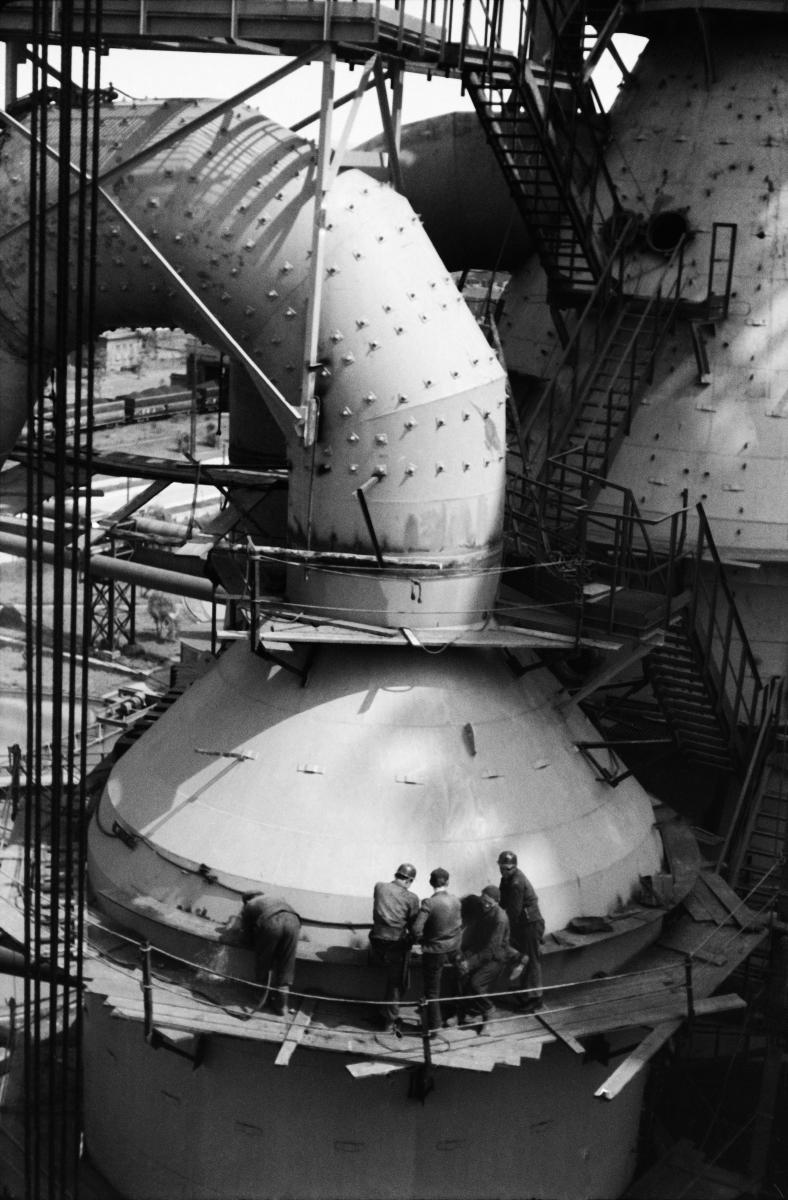 Grupa pracowników prowadzi prace naprawcze stojąc na balkoniku serwisowym ogromnej rurowej konstrukcji. Balkonik otacza blaszaną kopułę, z której skręcając wychodzi skręcająca w nieznanym kierunku około dwumetrowej średnicy rura.
