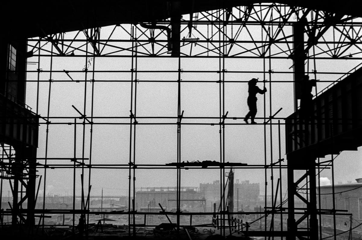 Dwóch mężczyzn w robotniczych strojach balansuje na rusztowaniu, w trakcie budowy ściany zewnętrznej hali fabrycznej. Ujęcie kontrastowe z jej wnętrza z widokiem na pozostałe obiekty na terenie kombinatu.