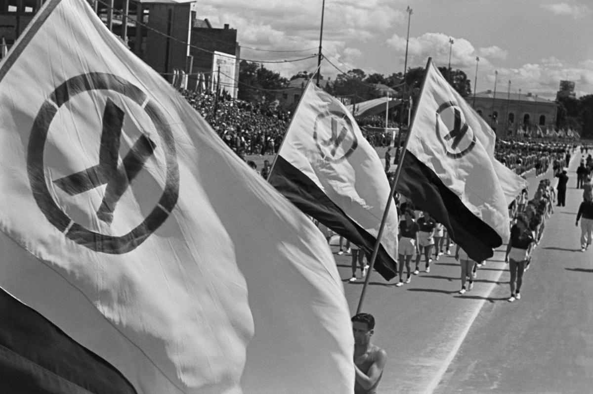 Uczestnicy pochodu na szerokiej aleji niosą flagi z literą K w kółku.