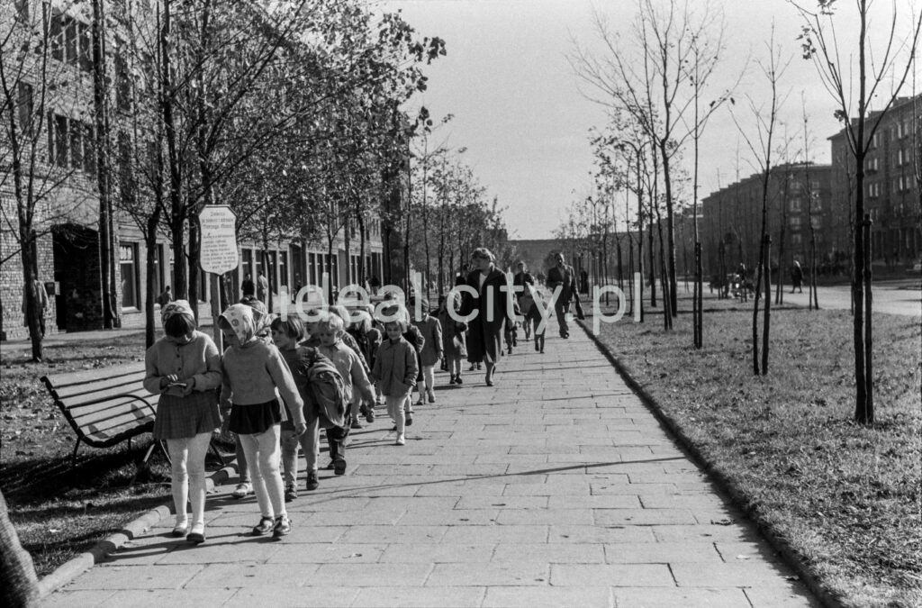 Children in school clothes march along the sidewalk that stretches along the green belt with residential buildings behind it.