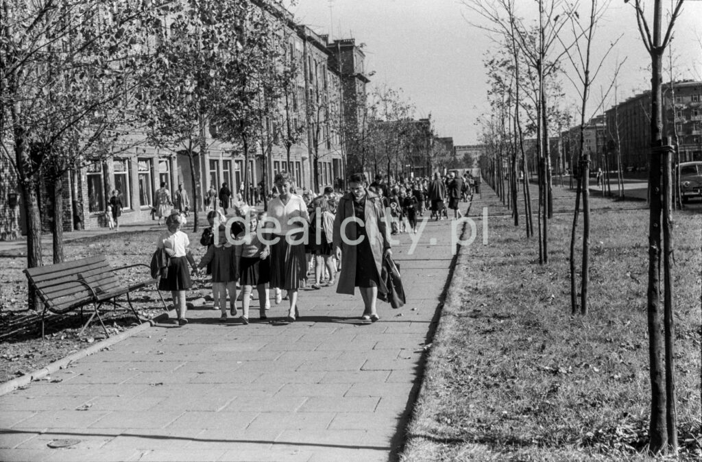 Children in school clothes are marching along the sidewalk that stretches along the green belt and residential buildings behind it, accompanied by two teachers at the front.