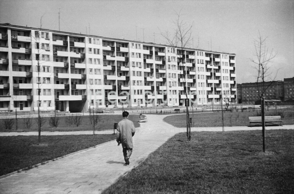A man in a trench coat walks dynamically along the pavement towards a wide, modernist block of flats.