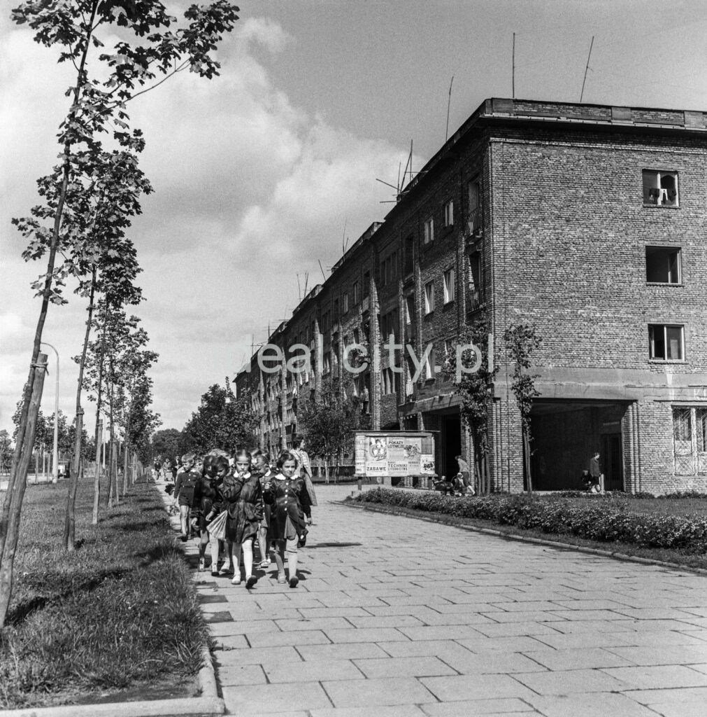 Children in school uniforms march along the paved sidewalk, on the right an unplastered brick apartment block.