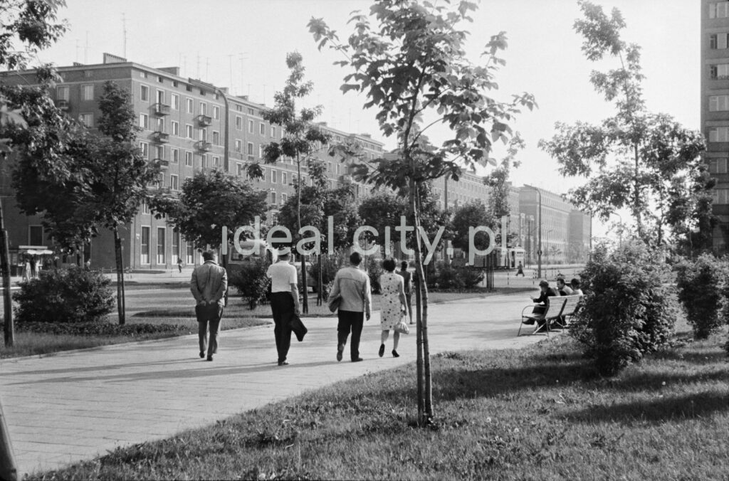 Rear shot of pedestrians walking along a wide sidewalk running through a green area, in the background the monumental buildings of the block.