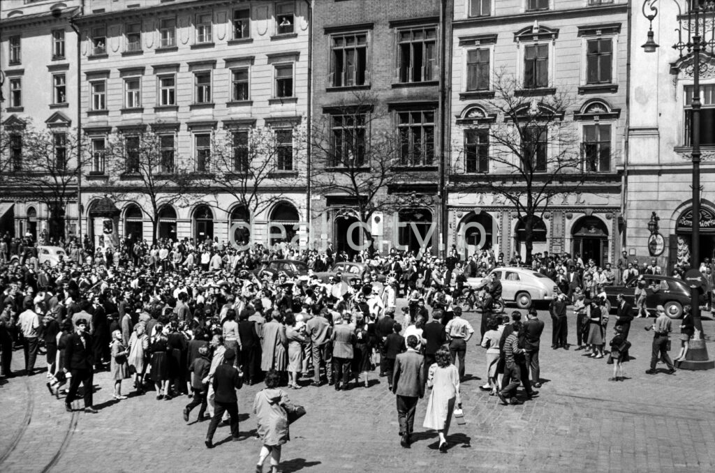 The crowd gathered in the town square, Renaissance tenement houses in the background.