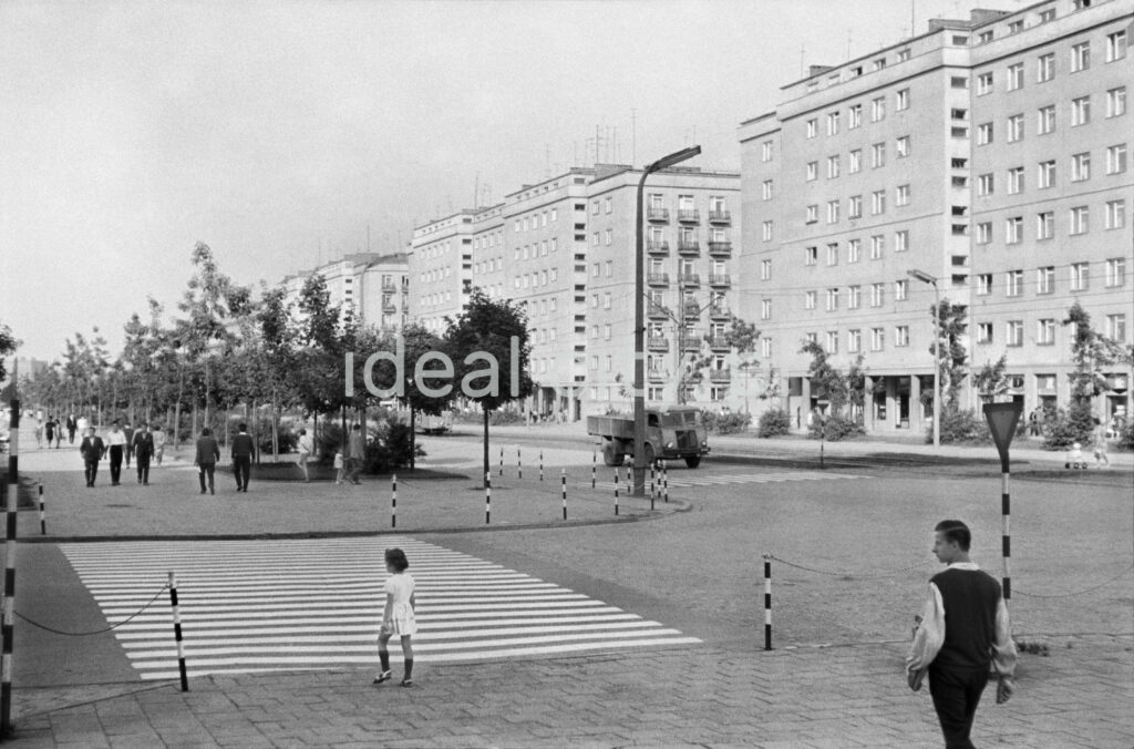 A girl in a white dress prepares to cross the wide pedestrian crossing, on the right a series of apartment blocks.