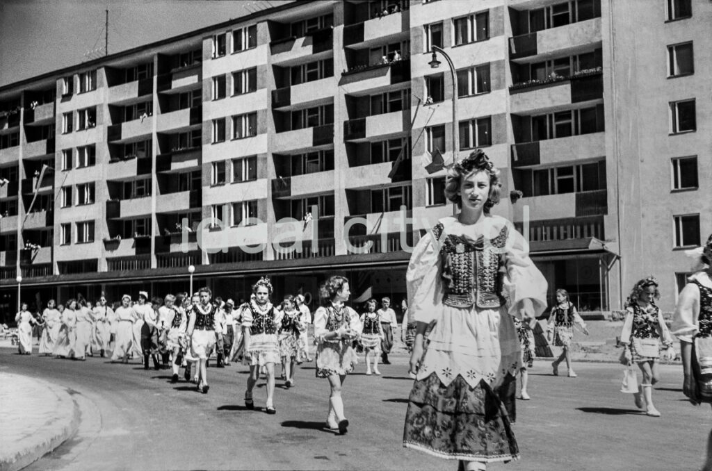 Girls in traditional folk costumes walk under a wide, modernist block.