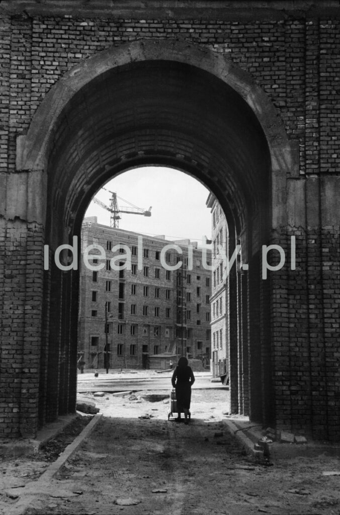 A woman with a pram goes through the massive gate of the building, another apartment block in perspective