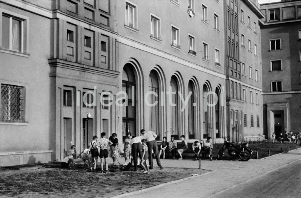 Inhabitants in everyday clothes during community work on the lawn in front of a monumental apartment block.