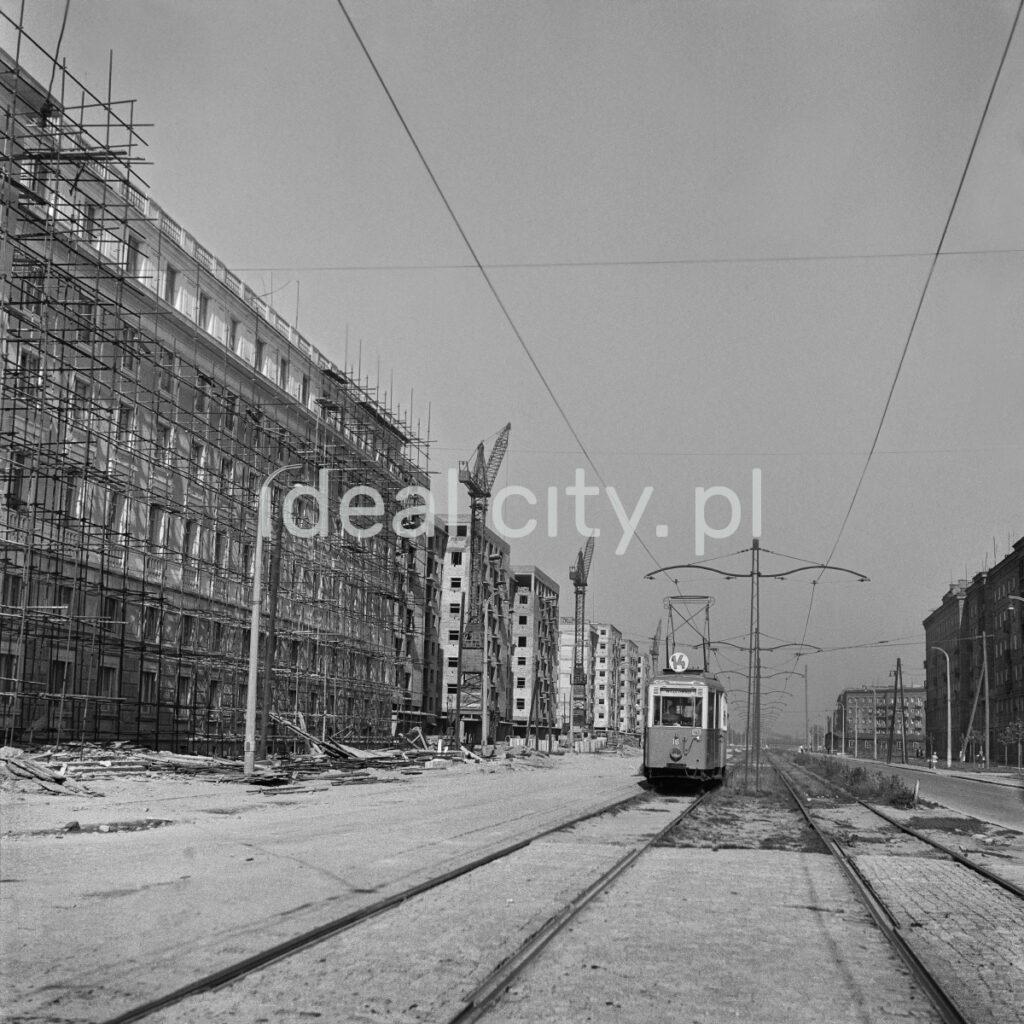 Tram number 14 runs along the track along the blocks hidden behind scaffolding.