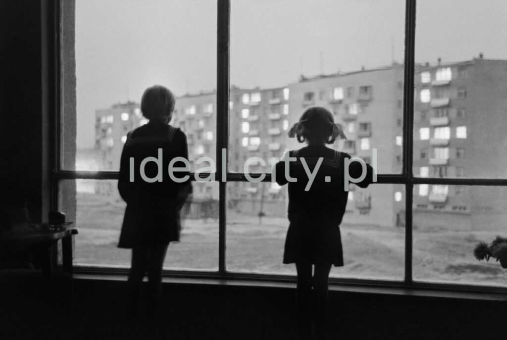 Two children watch the yard between the blocks through a panoramic window.