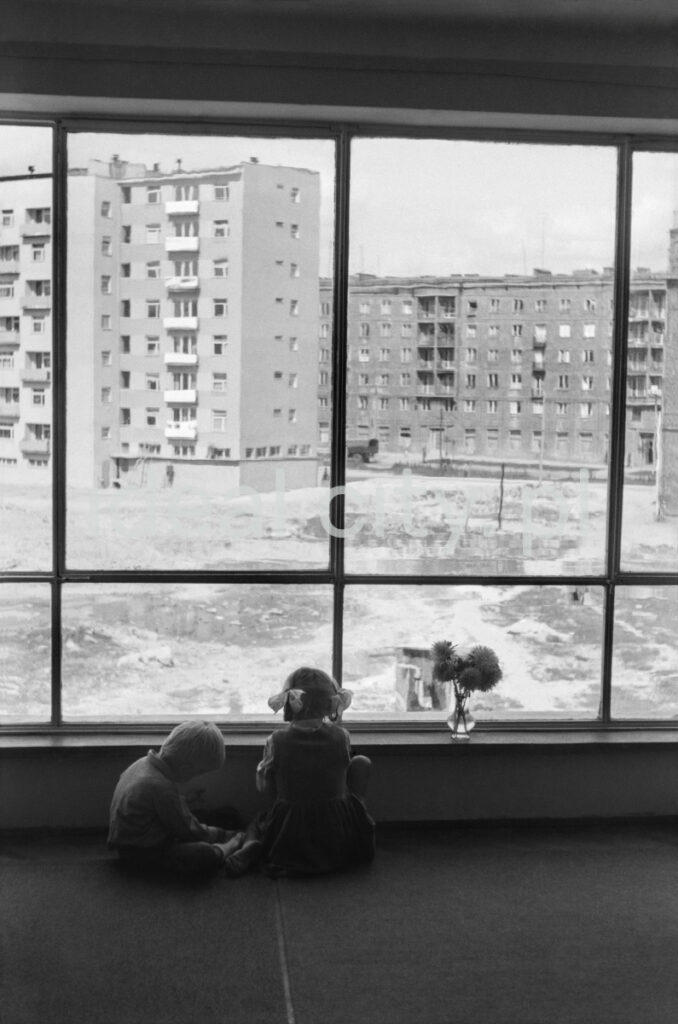 Two children are playing by the panoramic window, from which you can see the spacious yard between the blocks, there are flowers in a small vase on the windowsill.