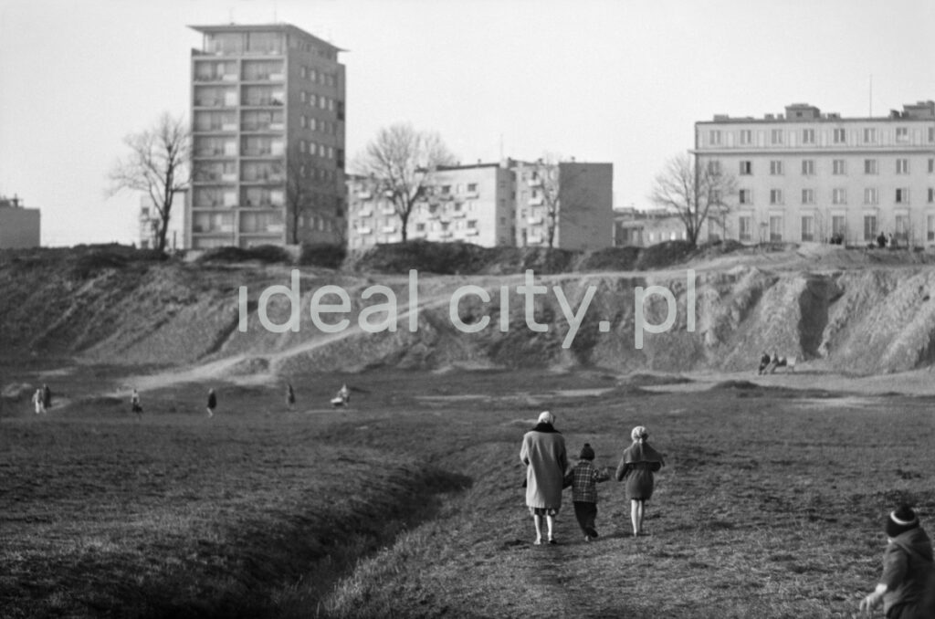 A woman with two children is walking along the meadow towards a tall block of flats located on the slope