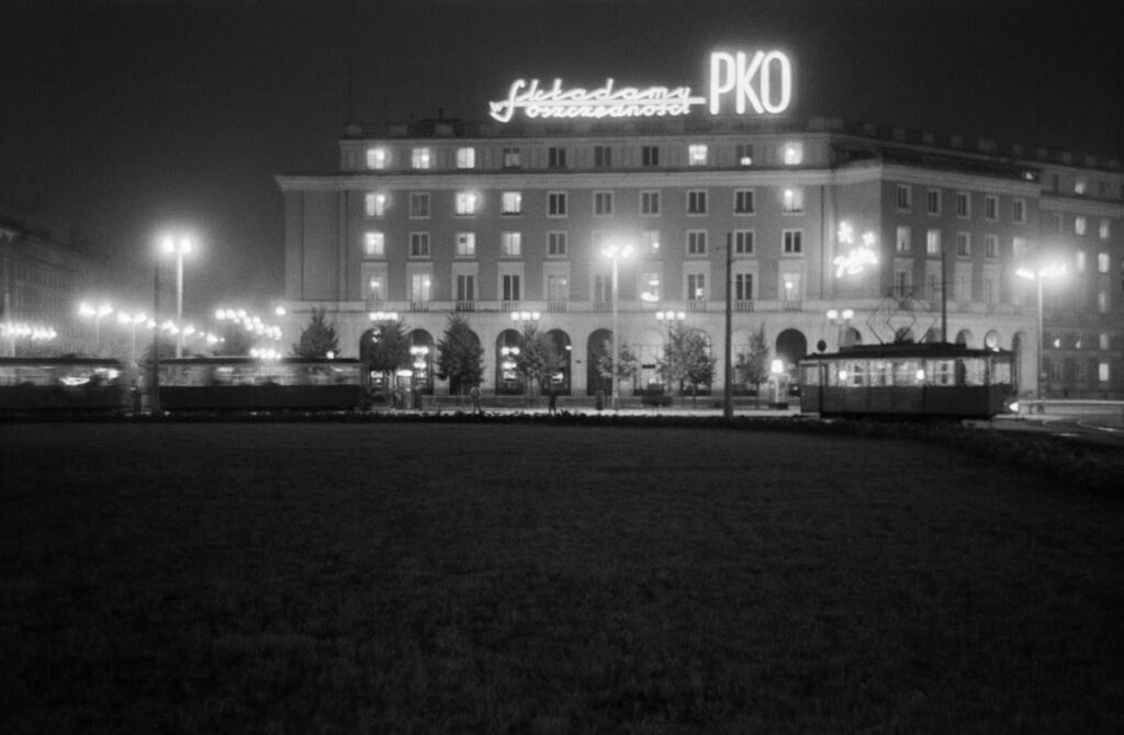 Night view of the large, illuminated city square with tram traffic, a neon sign at the top of the residential building: We are depositing at PKO.