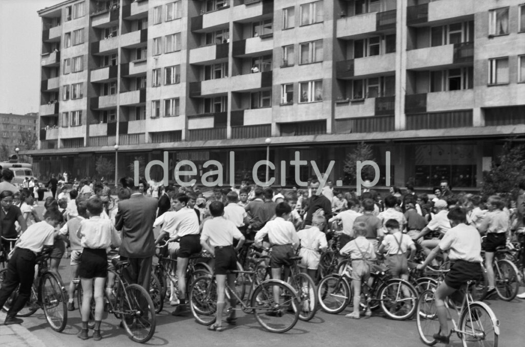 A group of white shirt cyclists in front of a wide modernist block of flats.