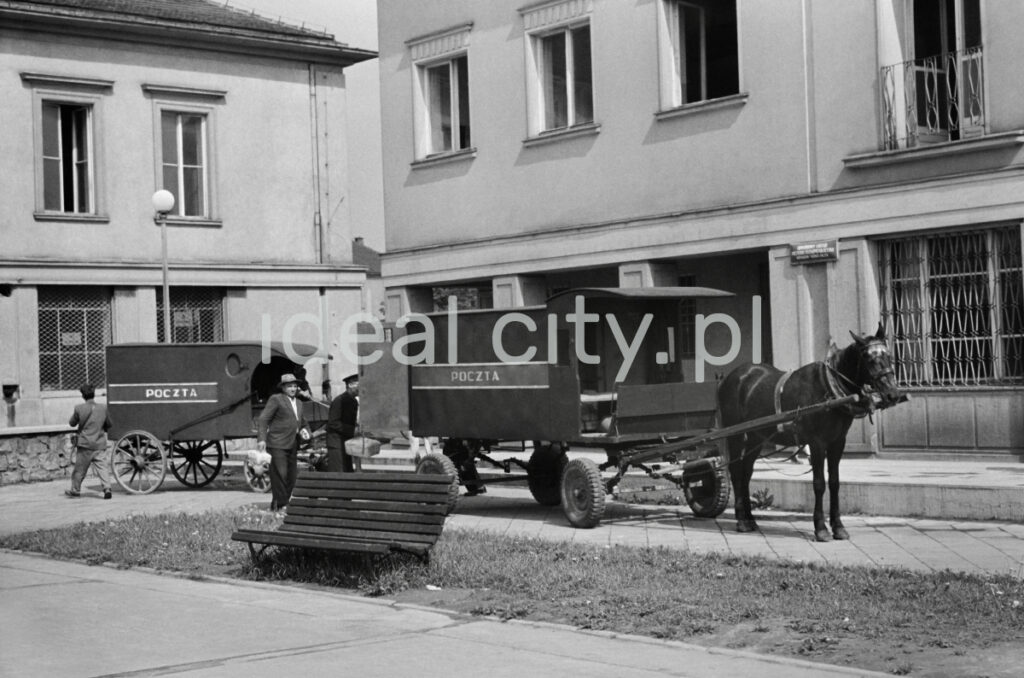 Two horse-drawn postal wagons are waiting for departure in front of the post office.