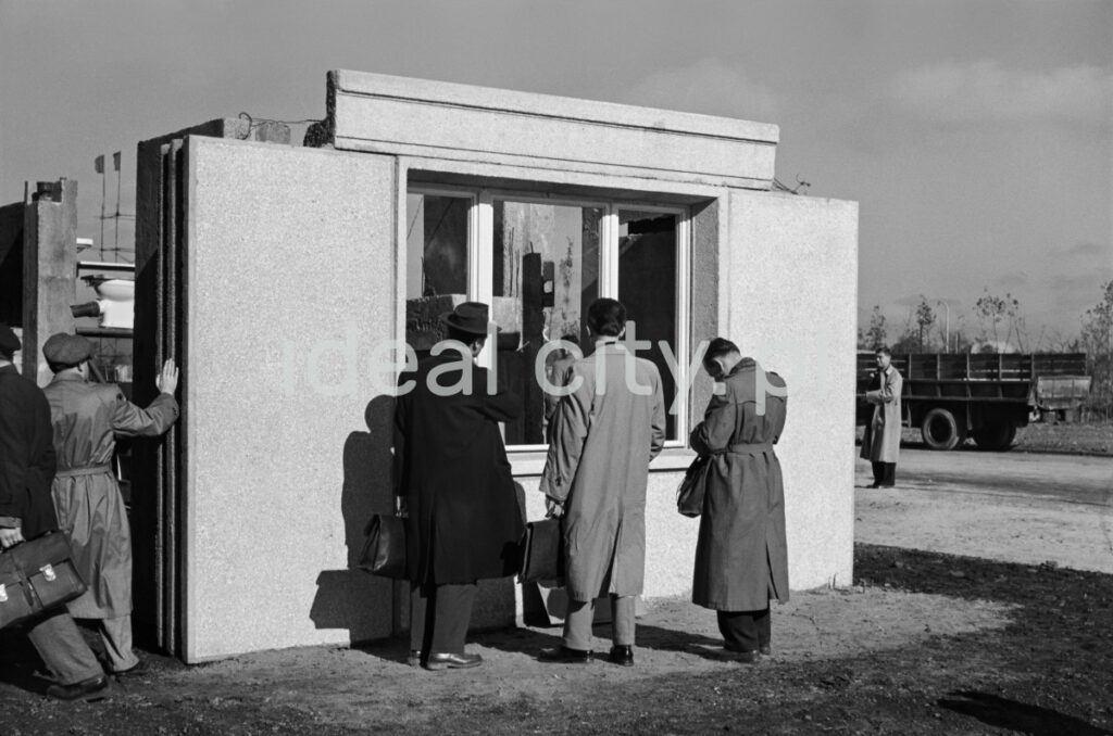 Men in coats are examining a prefabricated wall with a window set on the ground.