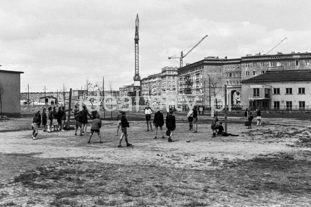 Children play volleyball on the pitch, with residential buildings and construction cranes in the background.