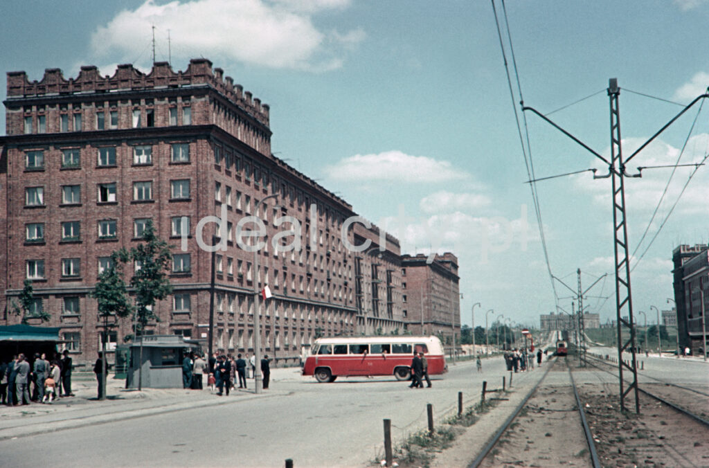 Traffic on the street with a tram line with a red bus passing in the center of the frame. On the left, a monumental brick apartment block.